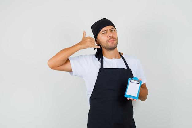 Bäcker mann, der mini-zwischenablage hält, zeigt telefongeste im t-shirt