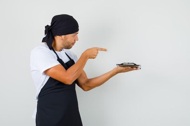 Bäcker mann hält tablett und zeigt auf die vorderseite von ihm im t-shirt