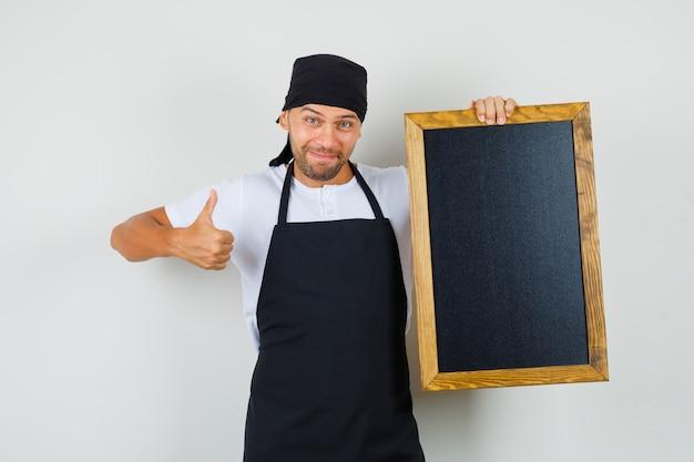 Bäcker mann im t-shirt, schürze hält tafel, zeigt daumen hoch und sieht glücklich aus