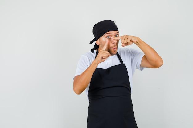 Bäcker mann im t-shirt, schürze zeigt auf sein augenlid