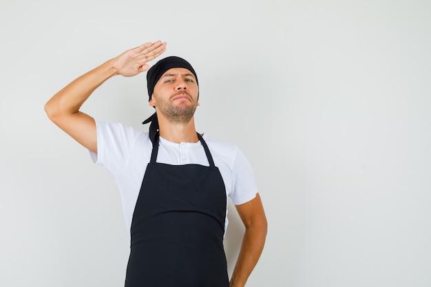 Bäcker mann im t-shirt, schürze zeigt grußgeste und sieht selbstbewusst aus