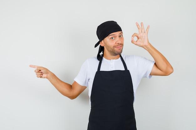 Bäcker mann im t-shirt, schürze zeigt ok geste