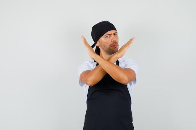 Bäcker mann im t-shirt, schürze zeigt stoppgeste und sieht entschlossen aus