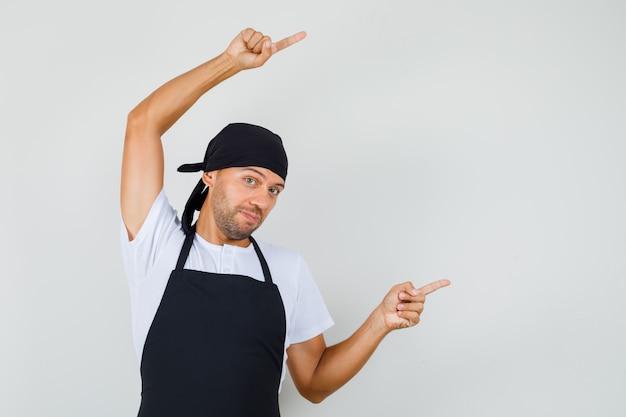 Bäcker mann im t-shirt, schürze zeigt weg und sieht optimistisch aus