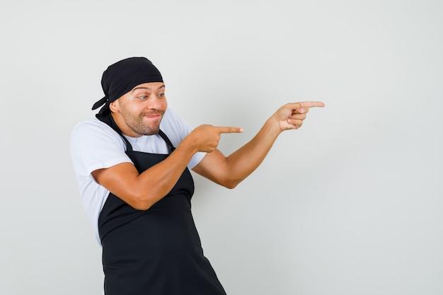 Bäcker mann im t-shirt, schürze zeigt zur seite und sieht munter aus