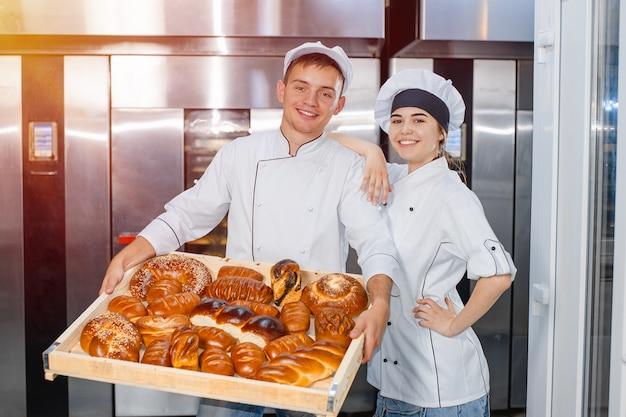 Bäcker mann und mädchen mit einem vollen kasten heißem gebäck in ihren händen