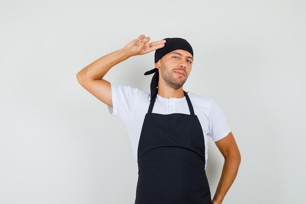 Bäcker mann zeigt hand und finger zum kopf im t-shirt
