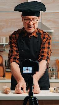 Bäcker mit hölzernem nudelholz für teig in der vorderen videokamera, die neue kochepisode aufzeichnet. alter blogger-koch-influencer, der internet-technologie verwendet, die in sozialen medien mit digitaler ausrüstung kommuniziert