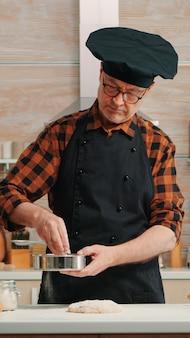 Bäcker mit knochen und schürze mit metallischem sieb, das zu hause backwaren zubereitet. glücklicher älterer koch mit küchenuniform mischen, besprühen, sieben von rohstoffen zum backen von traditionellem brot
