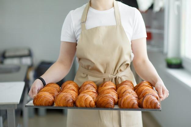 Bäcker tragen frisch gebackene knusprige goldene croissants auf einem metalltablett zum abkühlen. halten sie es an den seiten.