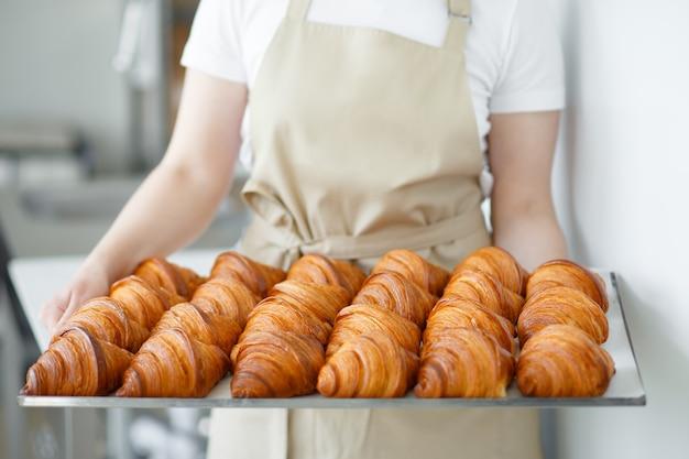 Bäcker tragen frisch gebackene knusprige goldene croissants auf einem metalltablett zum abkühlen