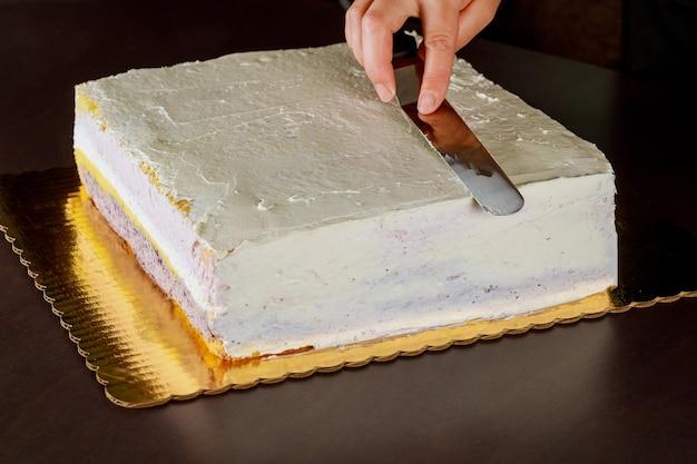 Bäckerabdeckung mit festlichem kuchen des weißen zuckergusses. schicht biskuit machen.