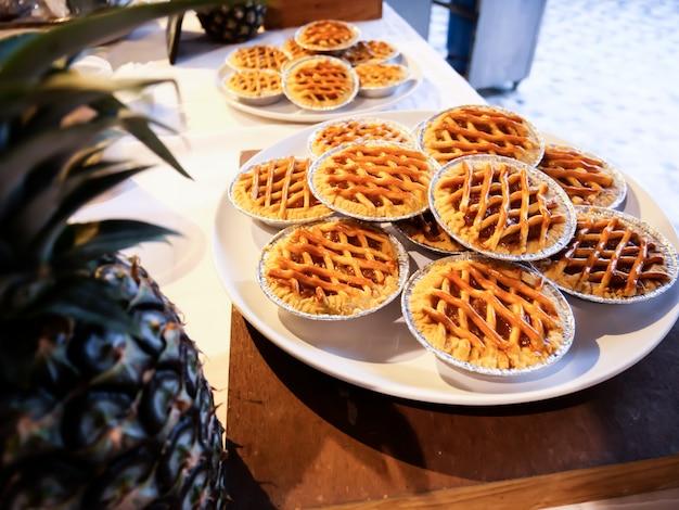 Bäckerarbeit ananas-torte oder frisch aus dem ofen gebackener apfelkuchen