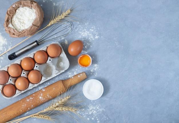 Bäckerarbeitsplatz mit mehl eier weizen und küchenwerkzeuge draufsicht mit kopienraum