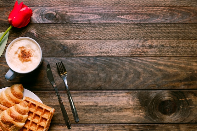 Bäckerei auf platte in der nähe von tasse getränk, blumen und besteck