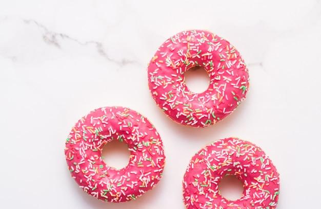 Bäckerei-branding- und café-konzept gefrostet bestreute donuts süßes gebäckdessert auf marmortischhintergrund donuts als leckere snack-draufsicht-lebensmittelmarke flach für blog-menü oder kochbuch-design