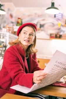 Bäckerei einbrechen. erfolgreiche stilvolle elegante geschäftsfrau, die ihre pause in der bäckerei verbringt, zeitung zu lesen