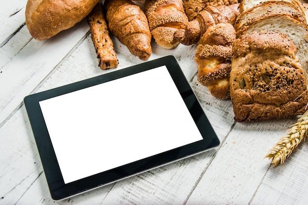 Bäckerei mit tablette auf hölzernem weißem hintergrund