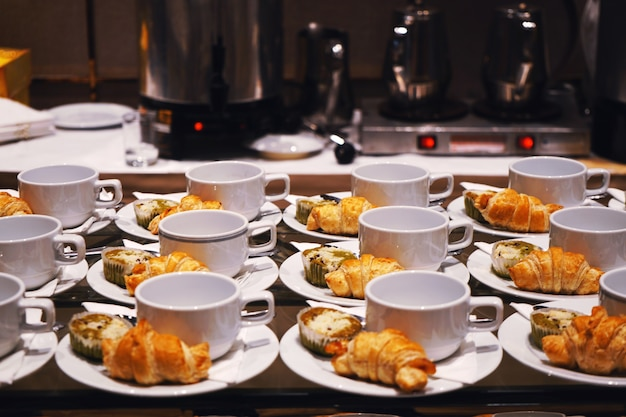 Bäckerei und getränk auf weißer schale und teller für kaffeepausenzeit.