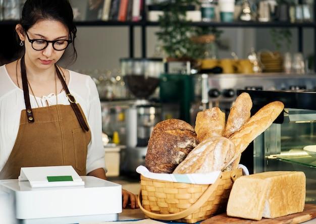 Bäckereiladeninhaber, der am zähler steht
