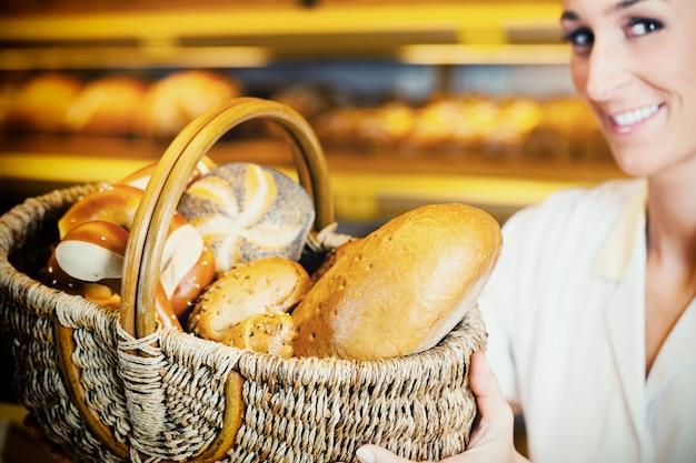 Bäckerfrau im unterstützer, der brot im korb verkauft