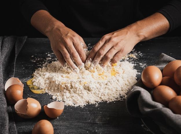 Bäckerhände, die eier mit mehl mischen