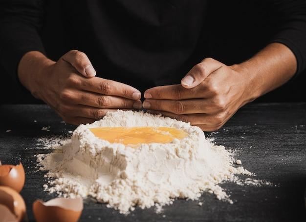 Bäckerhände, die eigelb mit mehl mischen