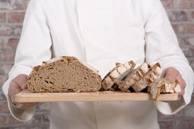 Bäckerhände mit frischem brot auf hölzerner tabelle