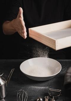 Bäckerhand, die mehl auf die oberseite siebt
