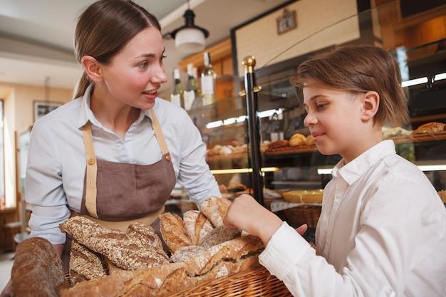 Bäckerin, die frisch gebackenes brot an einen jungen verkauft