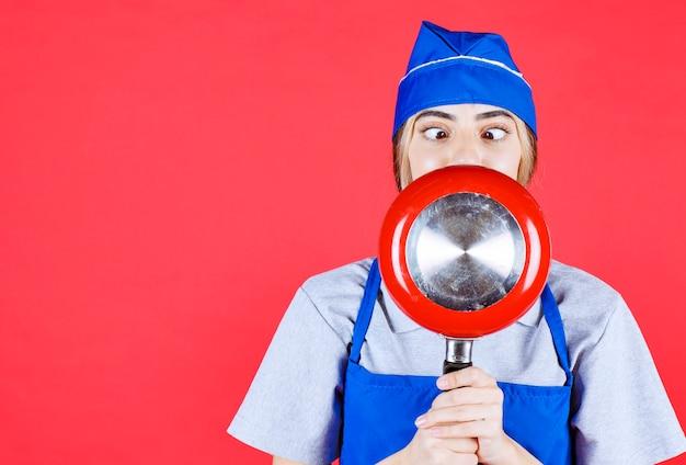 Bäckerin in blauer schürze, die eine rote bratpfanne vors gesicht hält