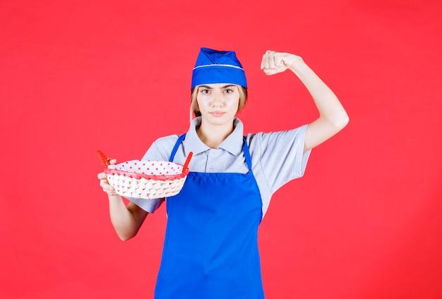 Bäckerin in blauer schürze, die einen brotkorb mit rotem handtuch im inneren hält und freudenhandzeichen zeigt