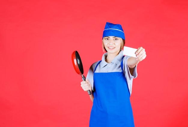 Bäckerin in blauer schürze hält eine tefal-pfanne und präsentiert ihre visitenkarte