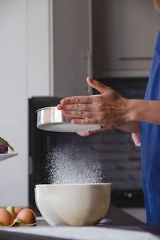 Bäckerin in blauer schürze siebt mehl in der heimischen küche, um das abendessen mit fliegendem mehl zuzubereiten