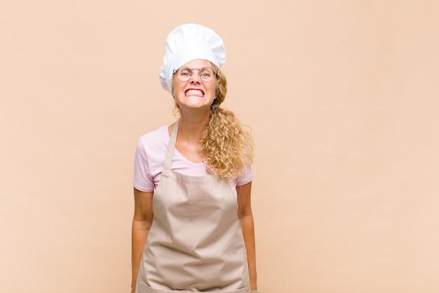 Bäckerin mittleren alters, die glücklich und doof mit einem breiten, lustigen, verrückten lächeln und weit geöffneten augen aussieht