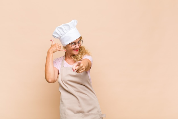 Bäckerin mittleren alters lächelt fröhlich und zeigt nach vorne, während sie einen anruf tätigen, den sie später gestikulieren und am telefon sprechen