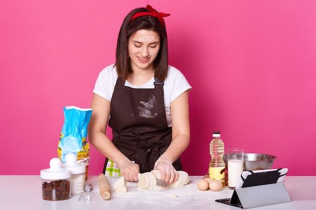 Bäckerin schneidet teig in kleine teile, bereit zum formen heißer brötchen, macht kuchen aus teig, trägt braune schürze, lässiges weißes t-shirt, rotes haarband, posiert isoliert über rosa wand.