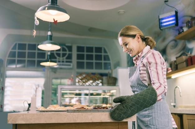 Bäckerin. schöne blonde bäckerin, die sich aufgeregt fühlt, während sie hart arbeitet und brötchen backt