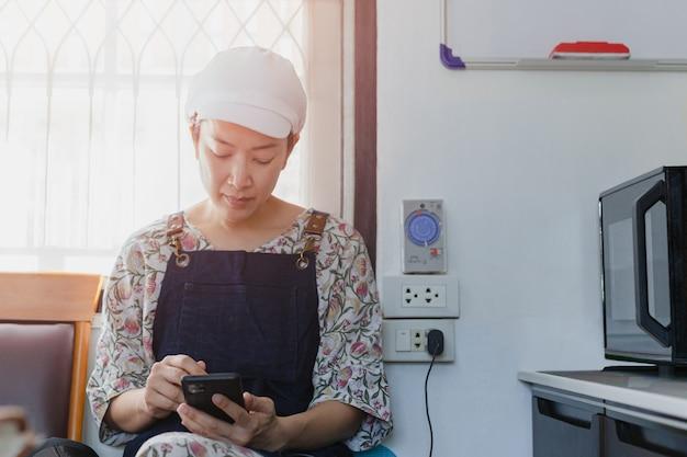 Bäckerin sitzt auf dem stuhl mit smartphone in der küche