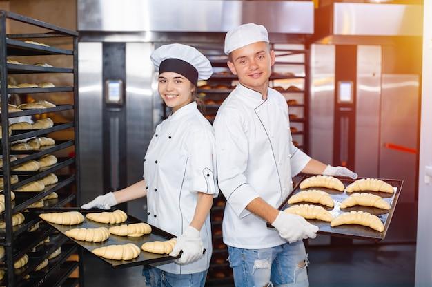 Bäckerjunge und -mädchen mit backblechen mit rohem teig