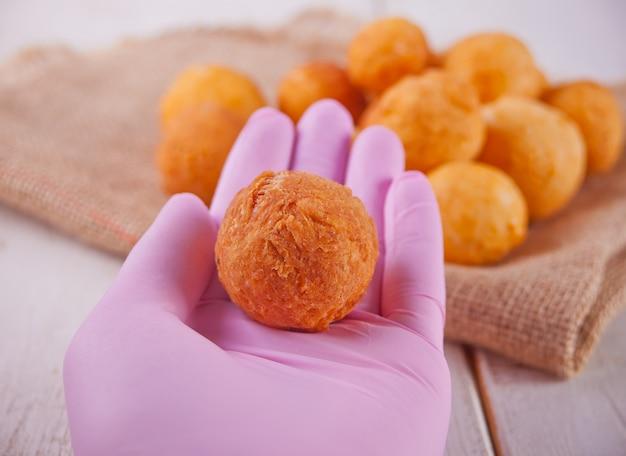 Bällchen der frisch gebackenen selbst gemachten hüttenkäsekrapfen und der hand der frau in den rosa handschuhen