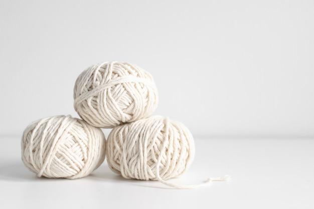 Bälle des weißen garns auf einem weißen wandhintergrund. fäden aus wolle boho bild. platz für text. gut für makramee- und handwerksbanner und werbung