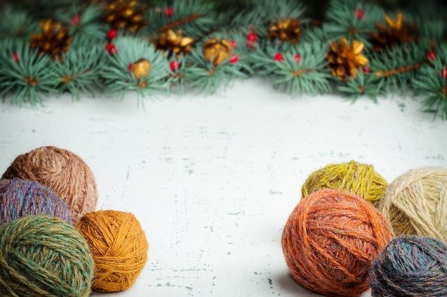 Bälle des wollgarns auf einem weihnachtsbaumhintergrund