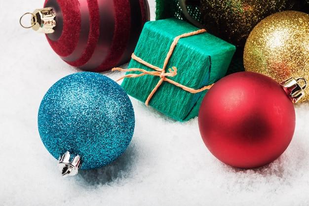 Bälle und geschenke auf dem schnee unter dem weihnachtsbaum