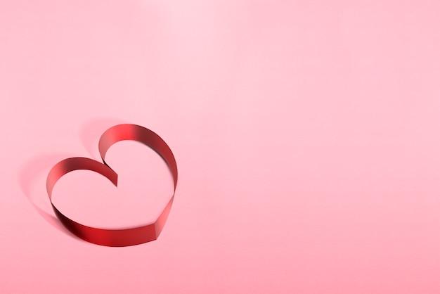 Bänder geformt als herzen über rosa hintergrund