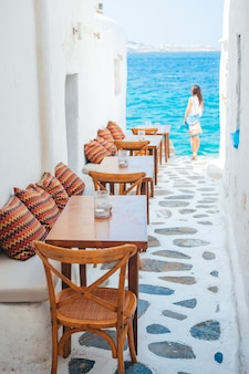 Bänke mit kissen in einem typischen griechischen straßencafé in mykonos mit herrlichem meerblick auf die kykladen