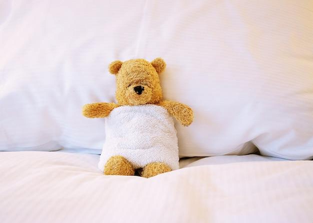 Bär trägt weißes handtuch auf dem bett.