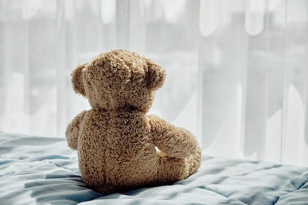 Bärenpuppe auf dem bett sitzen