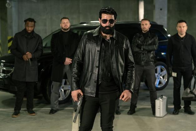 Bärtige kriminelle autorität in sonnenbrille, schwarzer lederjacke und jeans, die pistole mit seiner bande auf hintergrund halten