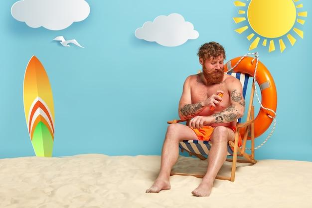 Bärtige rothaarige, die am strand mit sonnencreme aufwirft